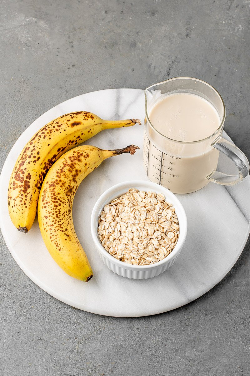 banana, rolled oats and almond milk on a round marble board