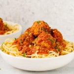 spaghetti and vegan eggplant meatballs in a white bowl by sweet simple vegan