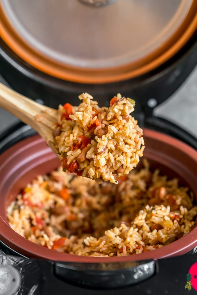 a spoon full of spanish rice and beans in a rice cooker.