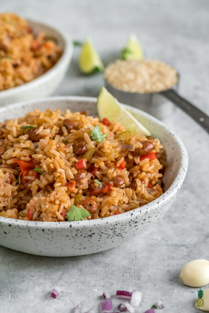 straight forward image of spanish rice and beans in a white bowl on grey background