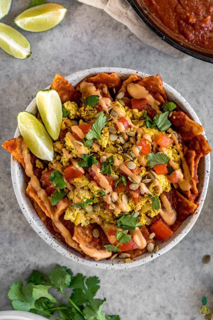 These vegan chilaquiles are spot on! They really do live up to being the BEST recipe, definitely a must try! Loaded up with a homemade red sauce, tofu scramble and chipotle crema, this is definitely a breakfast to impress a crowd. #vegan #chilaquiles #veganchilaquiles #veganbreakfast #mexican #veganmexican #veganized #party #brunch #musttry #tortillas #authentic