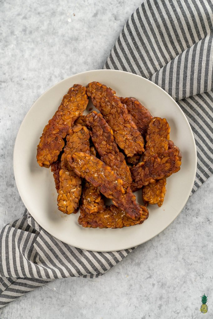 Making tempeh bacon at home is so easy and requires just 8 ingredients! Just whisk everything together, marinate it for a bit and cook it up to perfection. This is the perfect protein packed addition to your next breakfast! #tempeh #bacon #vegan #protein #easy #8ingredient #musttry #homemade #veganbreakfast #veganside #veganbacon #tempehbacon #howto #foolproof #easy