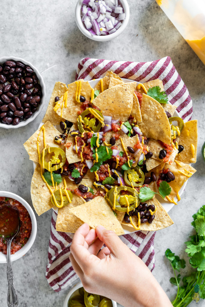 Classic Vegan nachos loaded up with homemade vegan queso, sweet simple beans, pickled jalapeños, guacamole, homemade restaurant-style salsa and so much more! These are perfect for parties and large gatherings, especially with Cinco de Mayo right around the corner! #vegan #nachos #classic #veganized #party #cincodemayo #veganmexican #vegancincodemayo #holiday #brunch #barbecue #family #kids #vegannachos #entree #lunch #snack