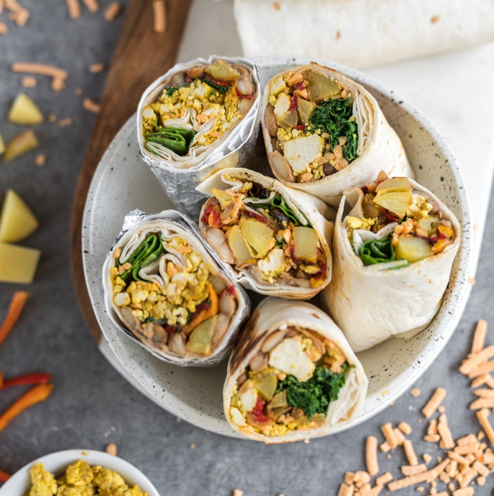 Easy and delicious vegan breakfast burritos that are loaded with breakfast potatoes, tofu scramble, homemade pinto beans and more! Plus, these burritos are freezer-friendly, so they make for the perfect make-ahead meal. #vegan #breakfast #burritos #loaded #freezerfriendly #onthego #bentobox #lunchbox #kids #veganlunch #tofuscramble #veganbreakfast