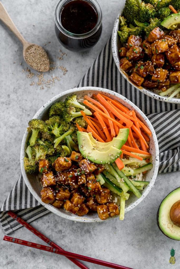 overhead image of teriyaki tofu bowls styled on a grey background.