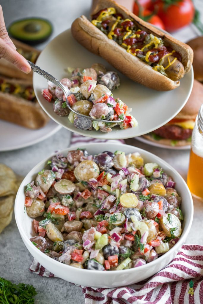 Memorial Day is coming up and we got you covered with the perfect party recipe! Your summer cookout this year will be taken to the next level with this bomb AF potato salad! Fresh veggies, herbs, and an amazing creamy vegan dressing; this potato salad is packed with flavor and appeals to just about anybody! #bbq #vegan #memorialday #easy #potatosalad #fresh #cookout #summertime #veganbbq #musttry #wholefoods #sweetsimplevegan