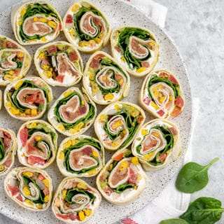 These easy 7-ingredient Mexican-Inspired pinwheels are a must try! They make for the perfect appetizer or lunch and are even great to take on the go! We love bringing these along with our summer picnics and packing them for school lunches. #vegan #appetizer #lunch #summer #picnic #onthego #mexican #inspired #pinwheel #bentobox #lunchbox #veganized #7ingredients