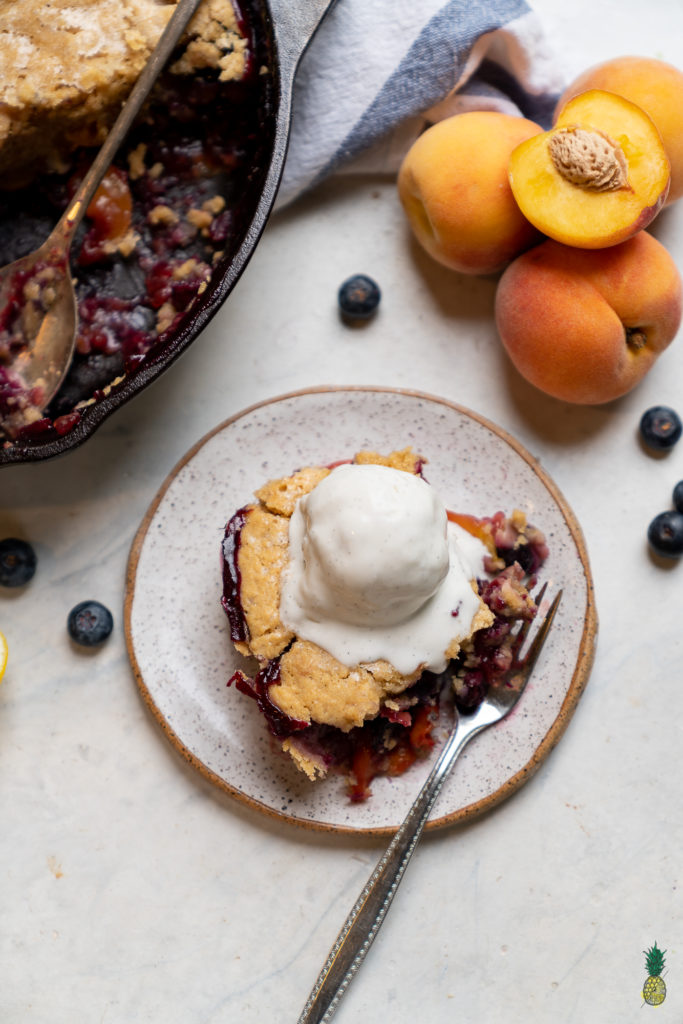 Atraditional peach cobbler brought to the next level with the addition of fresh blueberries and 100% plant-based ingredients. The perfect summer dessert ready in about an hour! #cobbler #vegan #veganized #bestofvegan #sweetsimplevegan #letscookvegan #musttry #vegansummerdessert #icecream #easyrecipe #peach #blueberry #cobbler #bakedgoods #easyvegan