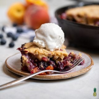 A traditional peach cobbler brought to the next level with the addition of fresh blueberries and 100% plant-based ingredients. The perfect summer dessert ready in about an hour! #cobbler #vegan #veganized #bestofvegan #sweetsimplevegan #letscookvegan #musttry #vegansummerdessert #icecream #easyrecipe #peach #blueberry #cobbler #bakedgoods #easyvegan