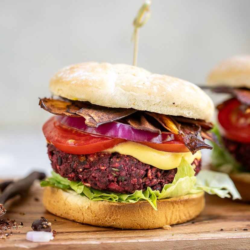 A flavor-packed,nutrient dense and protein-rich veggie burger that is the perfect dish to serve at a summer party. It is easy to make and can be prepared ahead of time and frozen for an easy meal! #summer #grilling #veganburger #beet #mushroom #veganprotein #entree #lunch #dinner #makeahead #frozen #mealprep #blackbeanburger #sweetsimplevegan