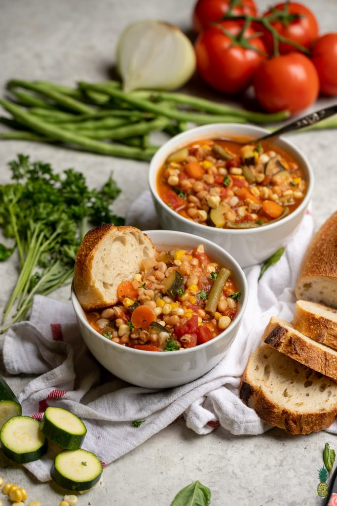 This is the perfect way to make use of the beautiful produce that is in season this summer. Zucchini, green beans, tomatoes, corn and so much more, this recipe is bursting with flavor and makes for the perfect appetizer or entree. Plus, this summer stew is ready in 30 minutes or less! #summer #stew #vegan #protein #whitebeans #entree #lunch #dinner #side #sppetizer #summerrecipe #veganyackattack #onthego #musttry #30minute #onepot