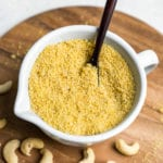 Learn how to make your own vegan parmesan cheese at home. It requires just 4 ingredients and only about 5 minutes of your time! Trust us, this recipe is a MUST TRY! #vegan #cheese #4ingredient #5minute #staple #vegancheese #kids #musttry #side #snack #entree #italian #parmesan #sweetsimplevegan