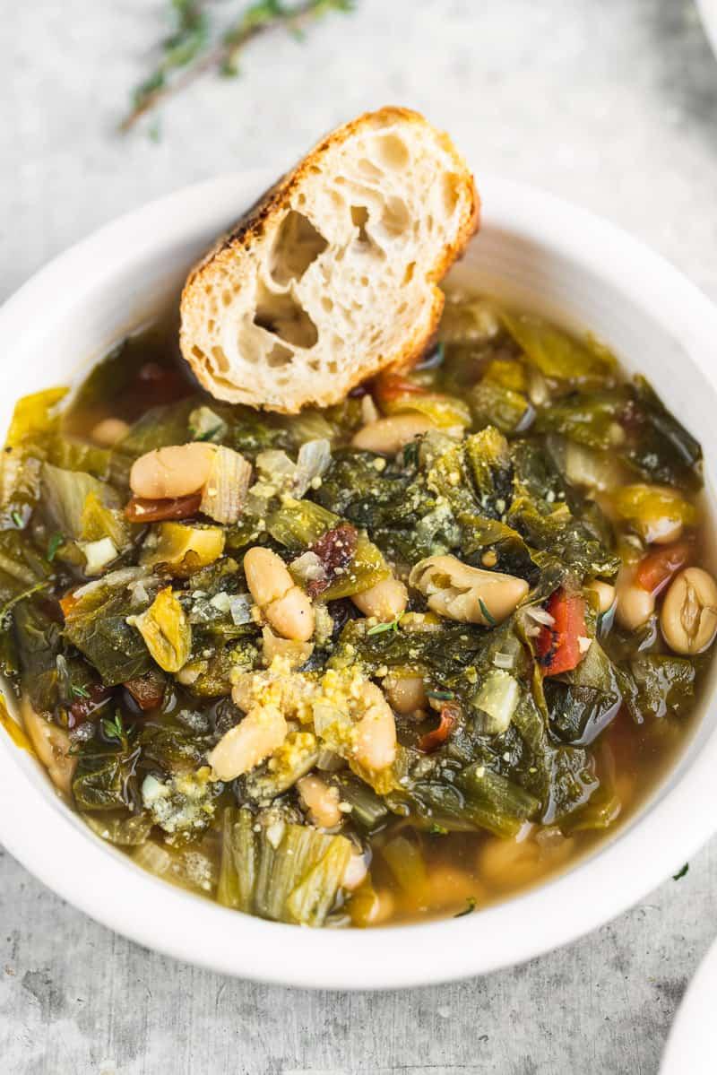 A close up shot of a vegan white bowl with white bean escarole soup