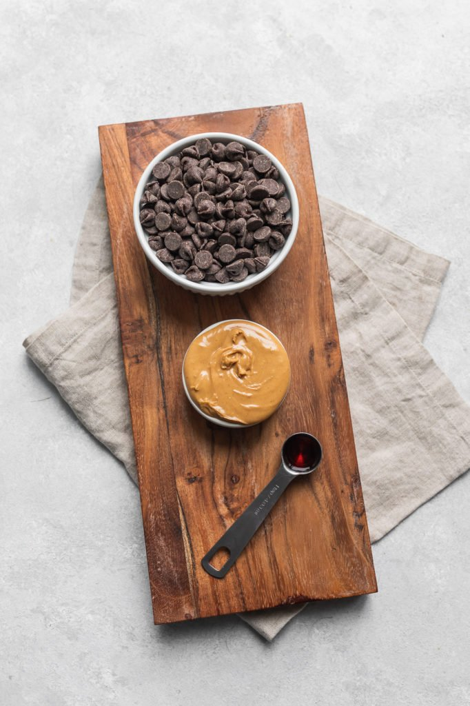 Peanut butter, chocolate chips and vanilla on a cutting board