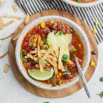 A bowl of vegan tortilla soup with garnishes and a spoon