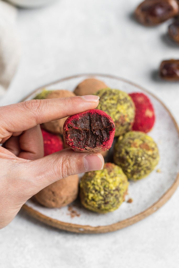 hand holding a biten into colorful vegan truffles on a serving plate