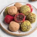 a biten into colorful vegan truffles on a serving plate