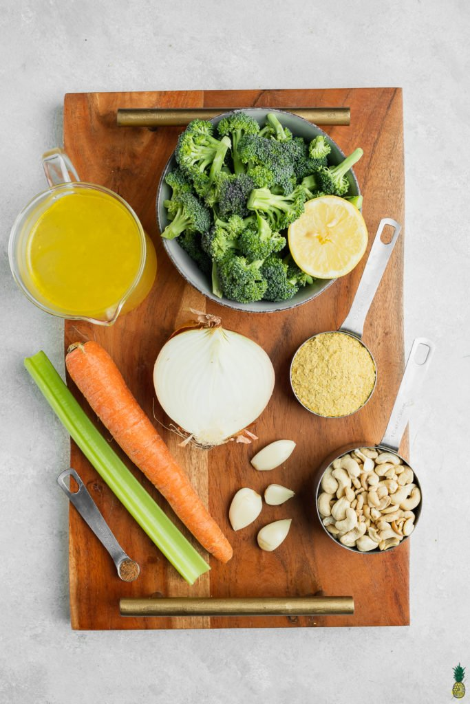 Ingredients for vegan broccoli cheddar soup on a wooden board