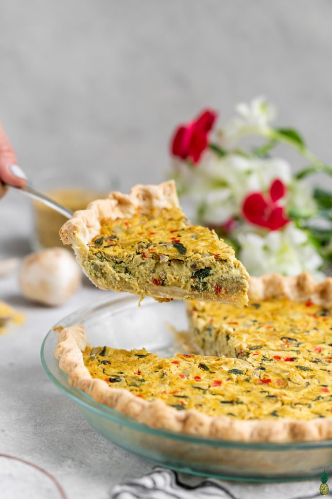 A cut shot of a vegan quiche coming out of a pan