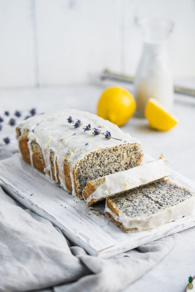 Gluten-free vegan lemon poppyseed loaf with a glaze slices on a cutting board is a delicious spring dessert.