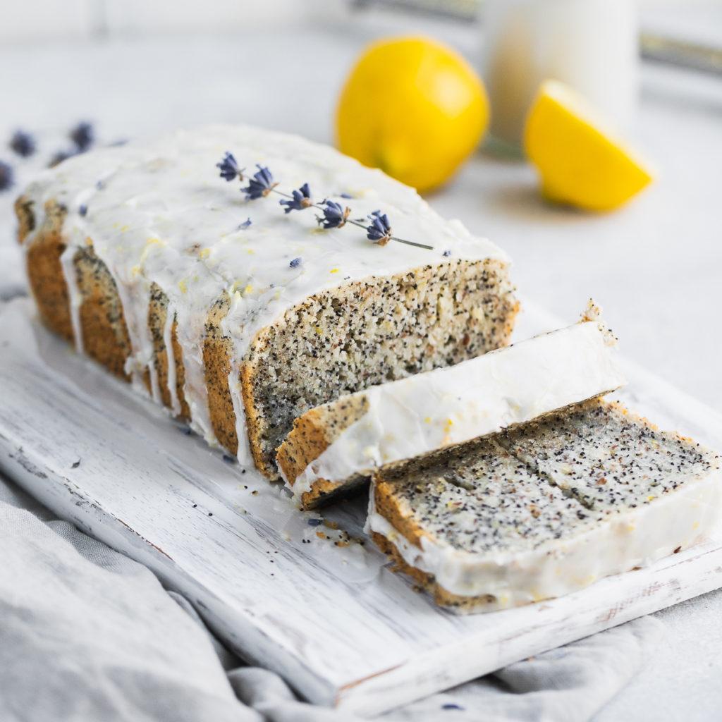 Gluten-free vegan lemon poppyseed loaf with a glaze slices on a cutting board