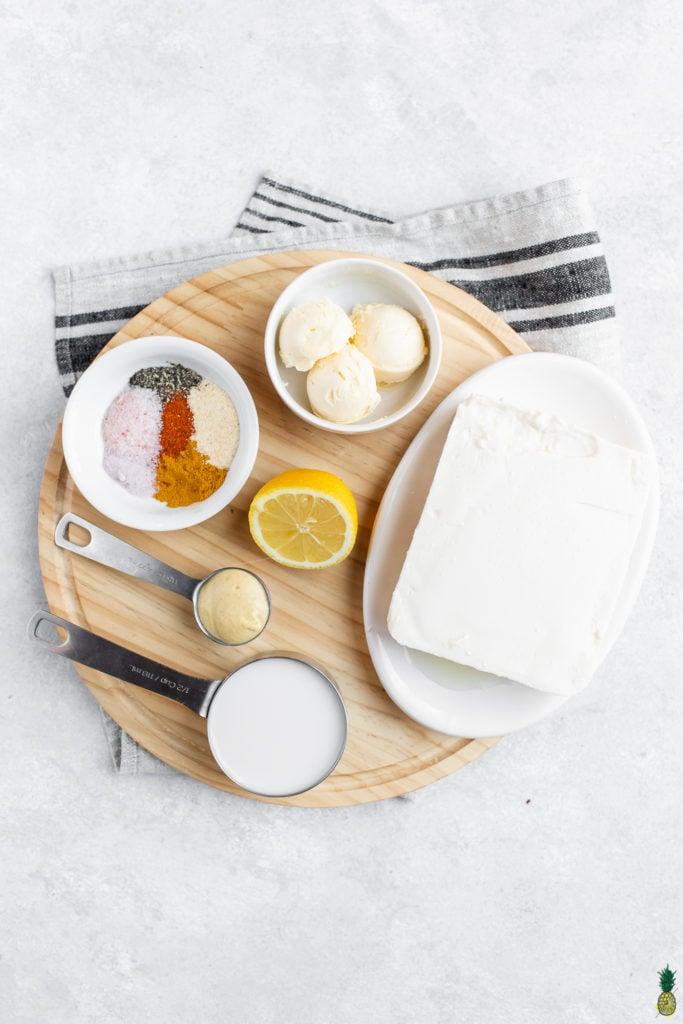Ingredients for vegan hollandaise ; lemon, vegan butter, almond milk, nutritional yeast, spices and tofu