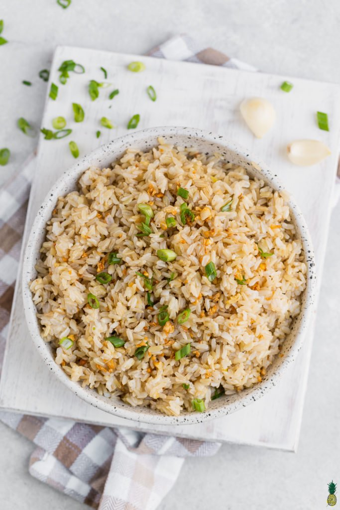 Vegan filipino garlic fried rice in a bowl with green onions and garlic on the side