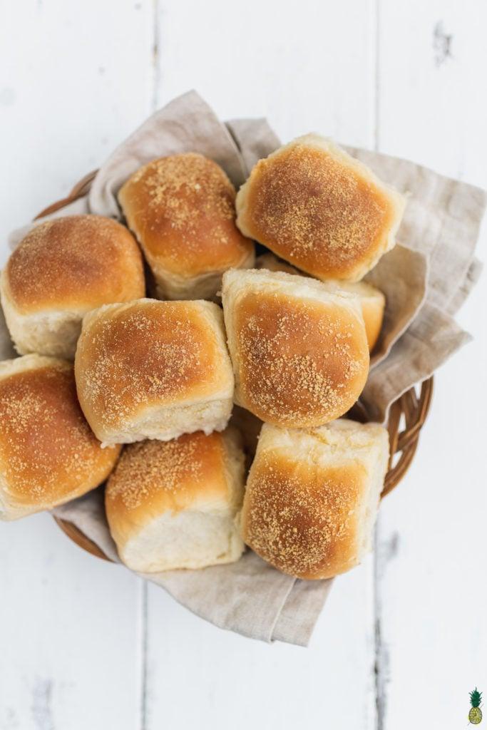 Vegan filipino pandesal bread rolls in a brown bread basket by Sweet Simple Vegan