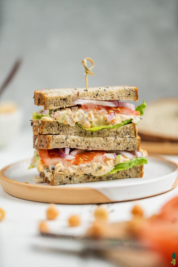Vegan chickpea tuna salad sandwich on a plate and cut on the Sweet Simple Vegan Blog