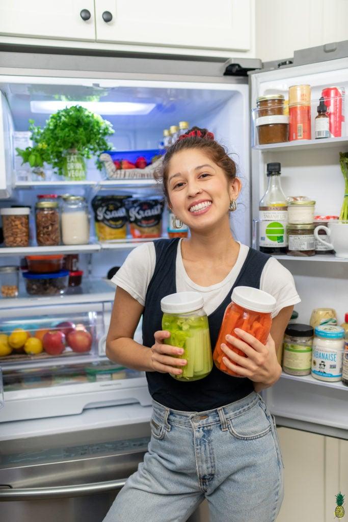 Standing in front of the open fridge with vegetables. Sweet Simple vegan fridge