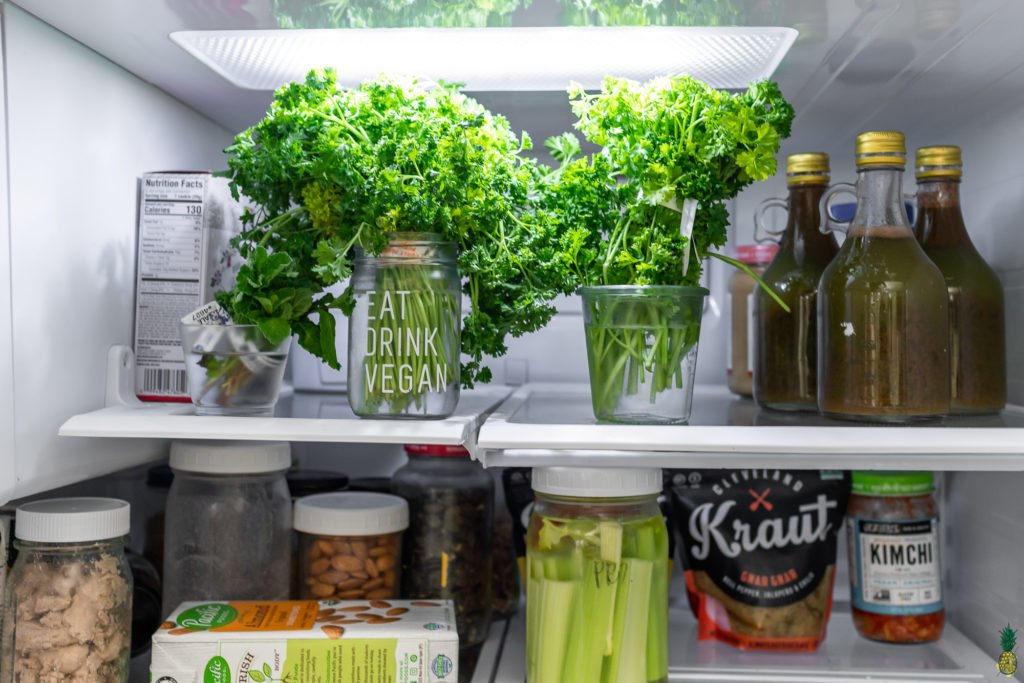 Herbs in jars with water in the refrigerator