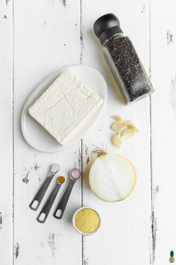 Ingredients to make an easy vegan tofu scramble on a wooden board by Sweet Simple Vegan