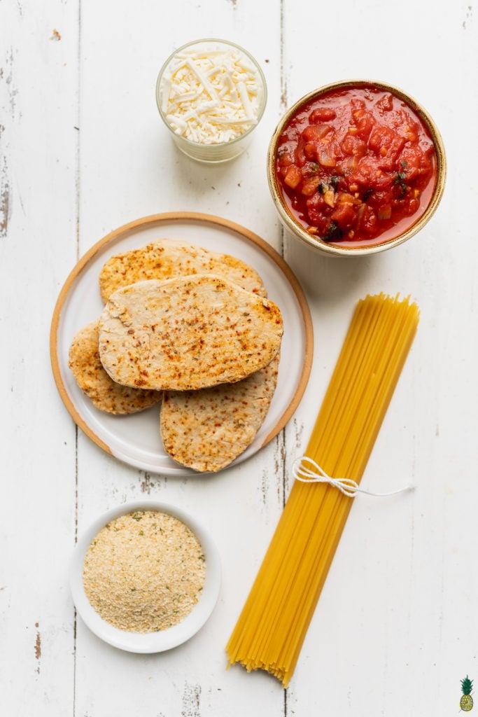 Ingredients to make vegan chicken parmesan on a wooden board by sweet simple vegan blog