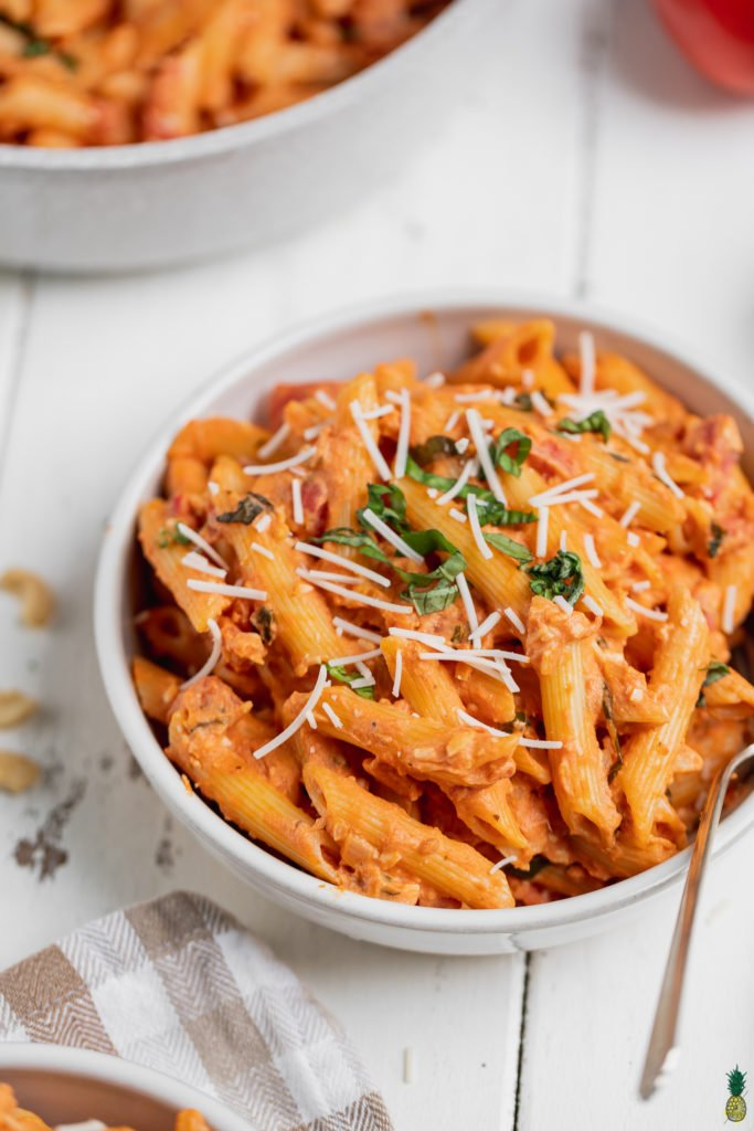 Macro shot of vegan penne alla vodka in a bowl with a fork by sweet simple vegan
