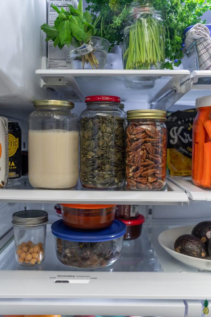 Nuts and seeds in jars in the refrigerator, sweet simple vegan fridge