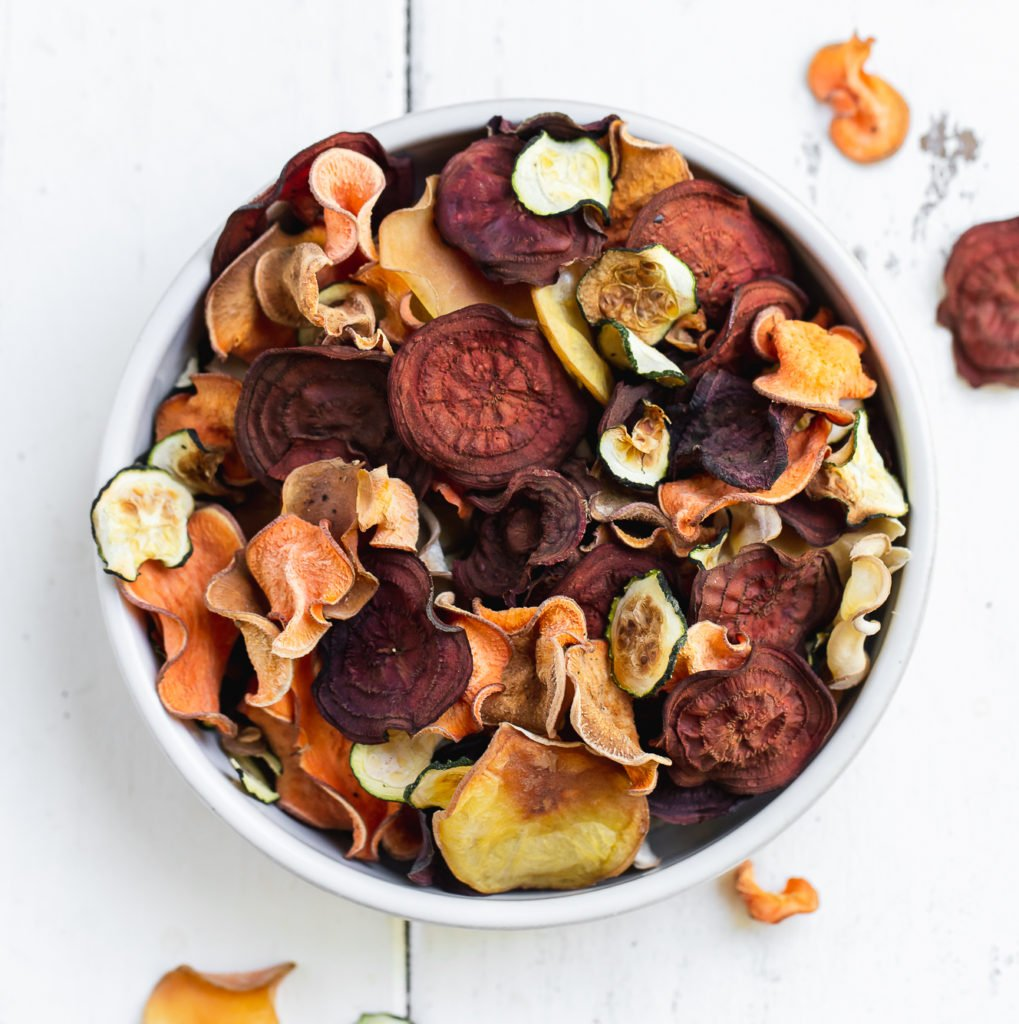mixed vegetable chips in a bowl on a white background by sweet simple vegan