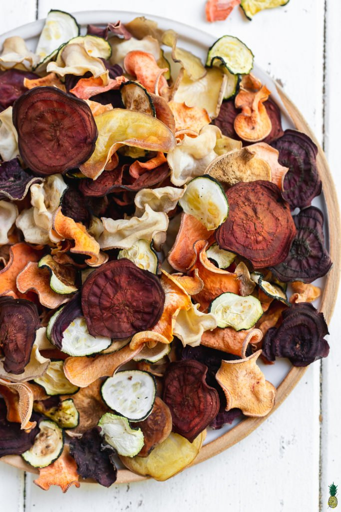 a close up of crispy mixed vegetable chips in a bowl on a white background by sweet simple vegan
