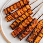 overhead photo of grilled barbecue tofu skewers on plate
