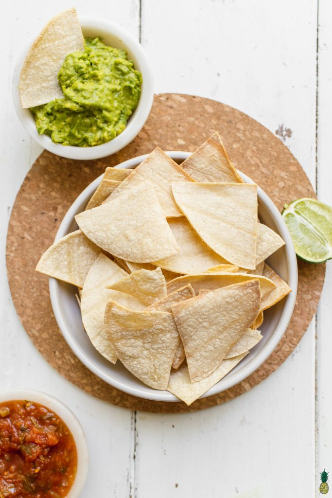 Homemade tortilla chips in a bowl on a cork board with guacamole, salsa and lime