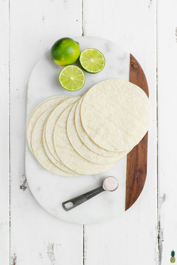 Tortillas, lime and salt on a marble board for homemade tortilla chips.