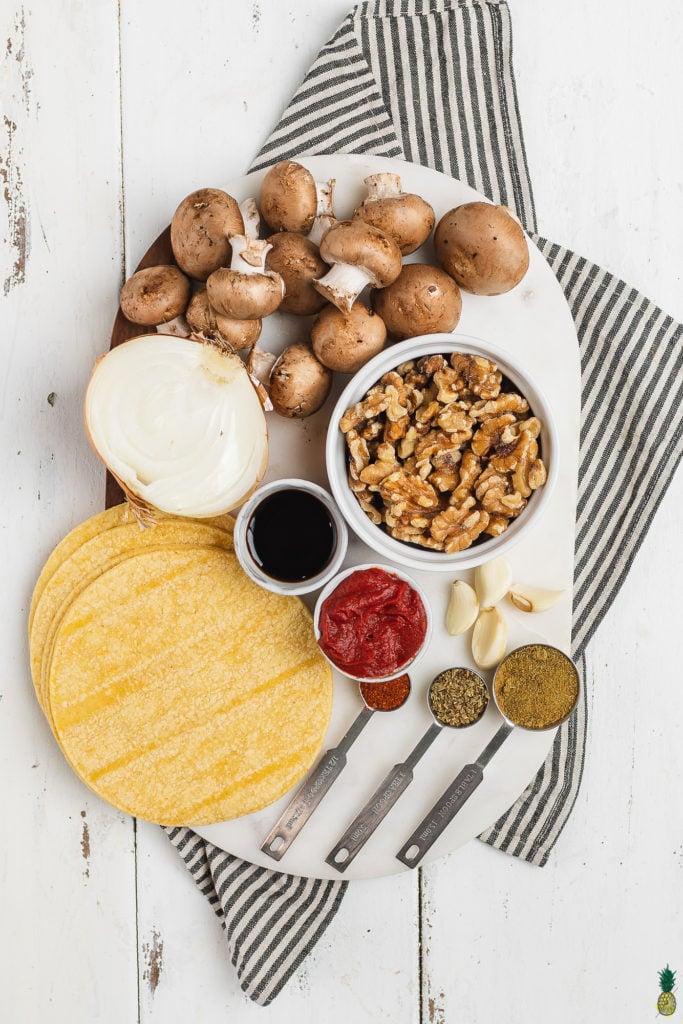 Ingredients to make vegan mushroom walnut taco meat on a marble board by sweet simple vegan