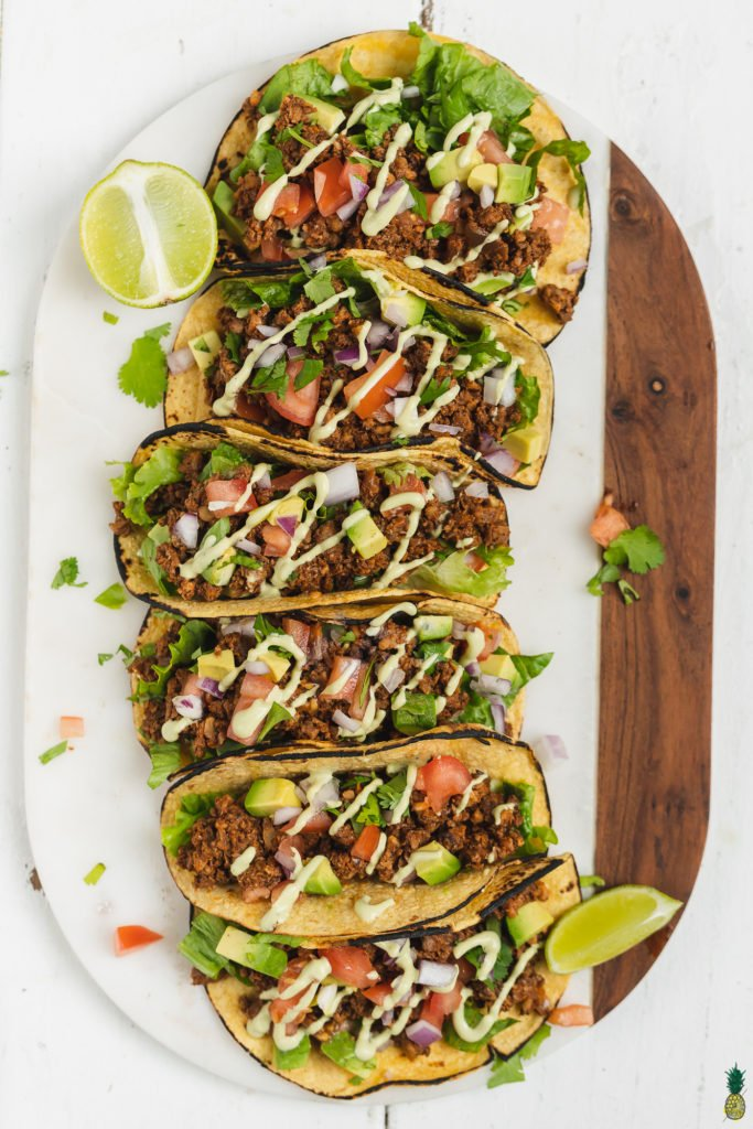 vegan mushroom walnut tacos filled with all of the toppings and served on a marble platter by sweet simple vegan