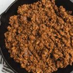 A close up shot of vegan mushroom walnut taco meat in a cast iron skillet by sweet simple vegan