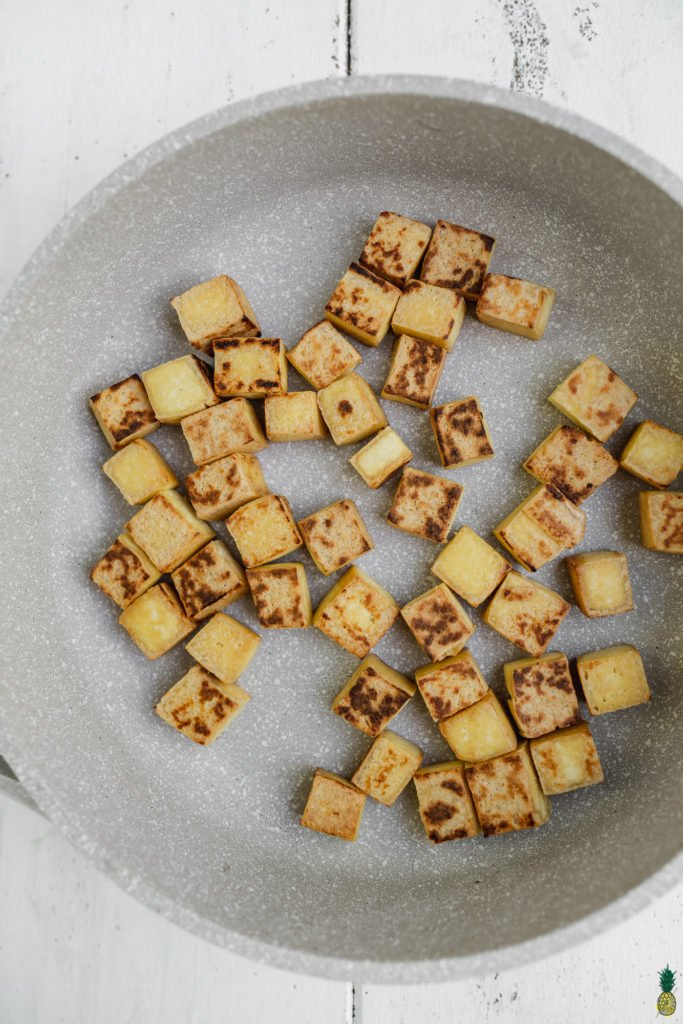Pan fried tofu golden brown on a non stick pan by Sweet Simple Vegan for Green Curry