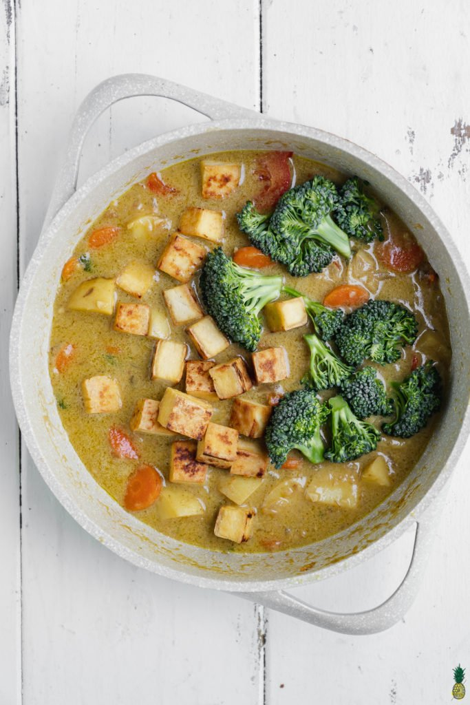 Tofu and broccoli for Thai green Curry being cooked in a non stick pan by Sweet Simple Vegan.