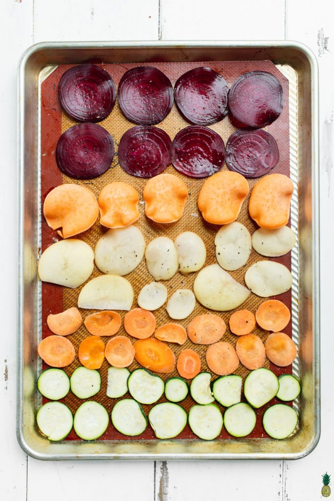 Thinly sliced vegetables on a baking sheet for homemade chips by sweet simple vegan