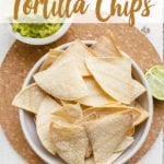 Homemade tortilla chips in a bowl on a cork board with guacamole, salsa and lime pinterest image
