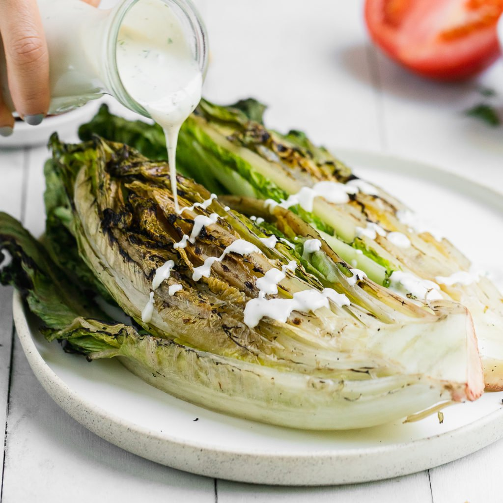 ranch dressing being poured onto grilled romaine lettuce