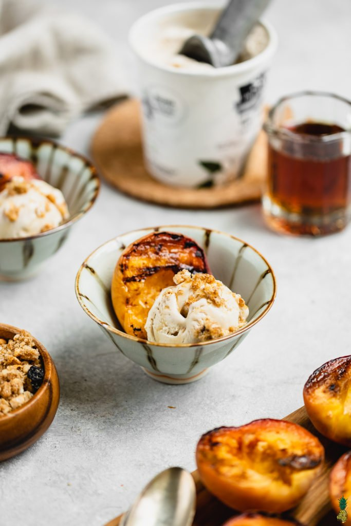 Maple glazed grilled peaches in a cup with vegan ice cream