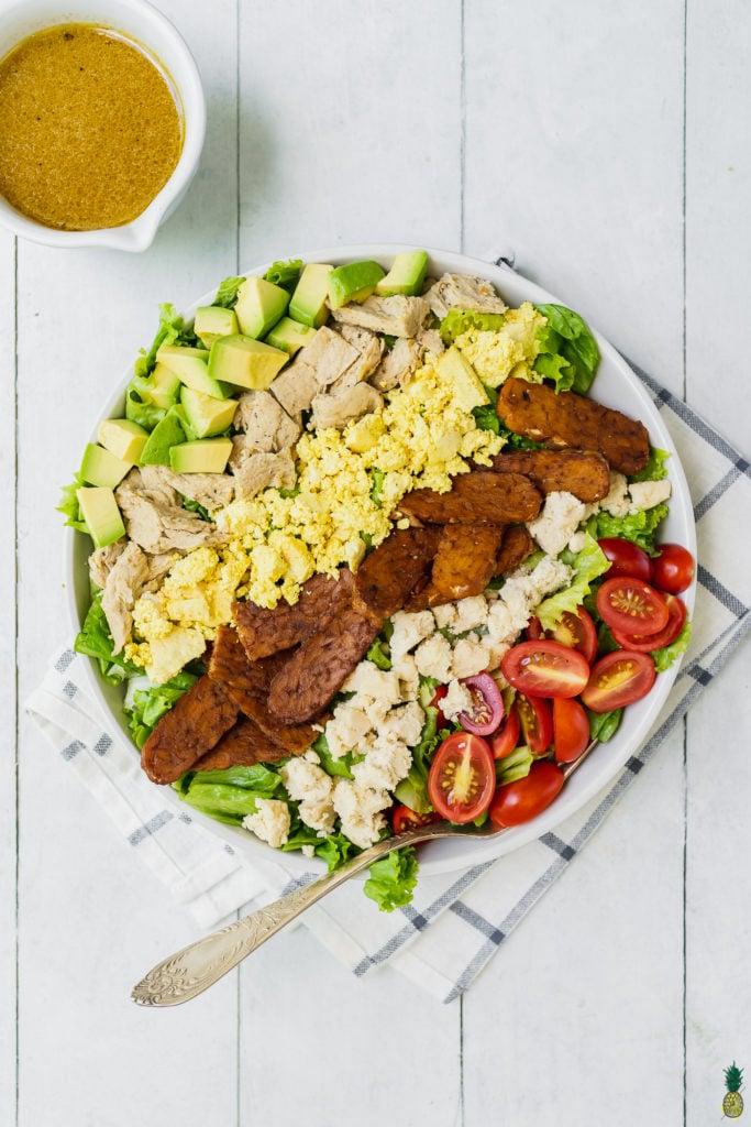 vegan cobb salad with tempeh bacon, tofu scramble, vegan feta cheese, vegan chicken and a vinaigrette on the side.